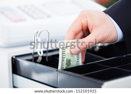 Close-up Of Hand With Dollar Notes Over Container - stock photo