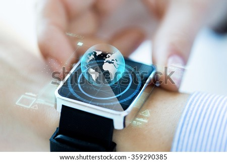 close up of hand with globe hologram on smartwatch - stock photo