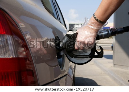 Close up of hand with gloves using petrol pump and filling Diesel / Fuel on her car - stock photo