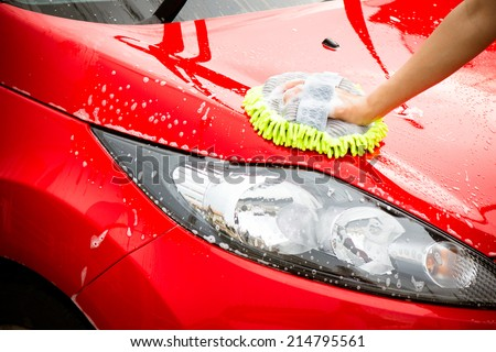 Close-up Of Hand With green Brush Washing Red Car - stock photo
