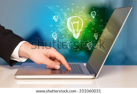 Close up of hand with laptop and glowing idea bulb - stock photo