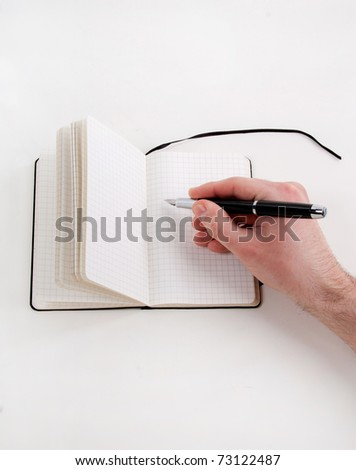 Close-up of hand writing in notebook - stock photo