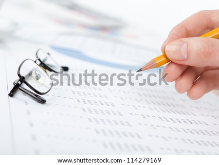 Close up of hand writing in the document with pencil. Glasses lying on the paper - stock photo