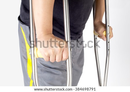 Close-up of handicapped man holding crutches on white background.  - stock photo