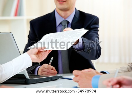 Close-up of handing over documents during business briefing - stock photo