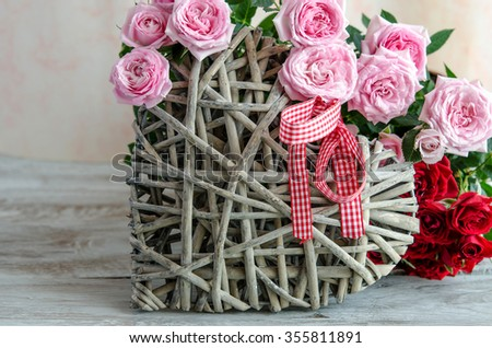 Close-up of handmade wooden heart decorated with red and pink roses on table - stock photo