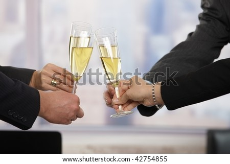 Close-up of hands: business people raising toast with champagne focus placed on flutes. - stock photo