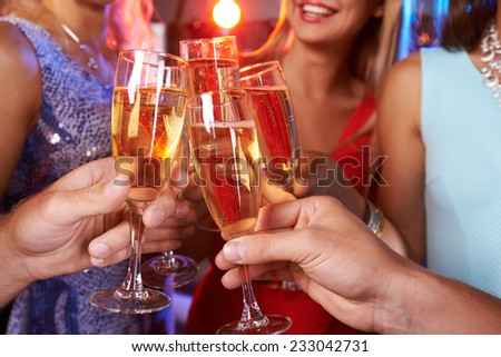 Close-up of hands clinking champagne flutes - stock photo
