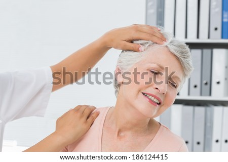 Close-up of hands doing neck adjustment in the medical office - stock photo