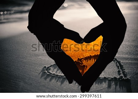 Close up of hands forming heart against one heart drawn in the sand - stock photo