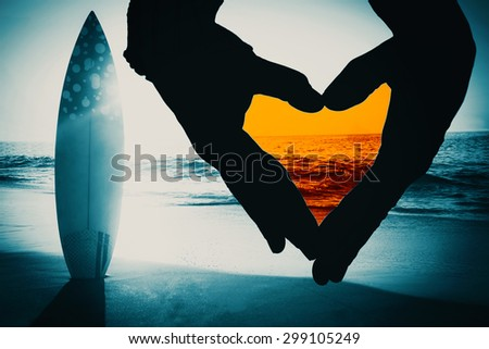 Close up of hands forming heart against surf board standing on the sand - stock photo