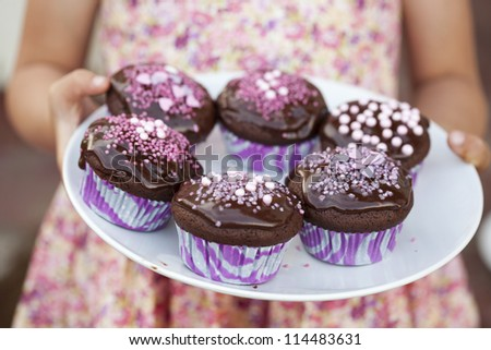 Close-up of hands holding a plate of delicious chocolate cupcakes with chocolate icing and sprinkles - stock photo