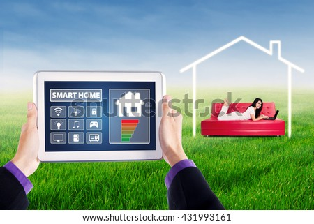 Close up of hands holding a tablet with smart house controller applications, shot with young woman using laptop on sofa at field