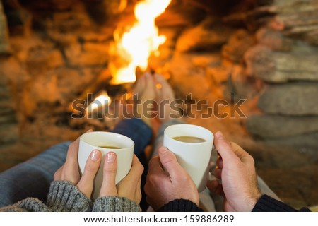 Close-up of hands holding coffee cups in front of lit fireplace - stock photo