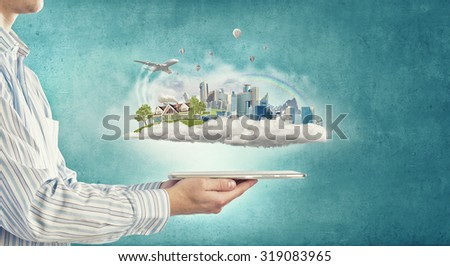 Close up of hands holding image of modern cityscape  - stock photo