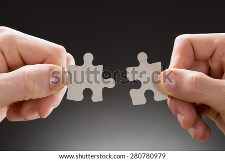 Close-up Of Hands Holding Jigsaw Pieces On Grey Background - stock photo