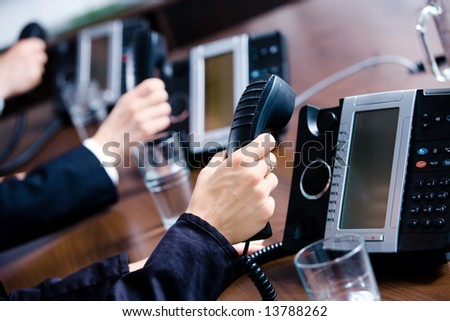 Close-up of hands holding landline phone receivers at customer service office. - stock photo