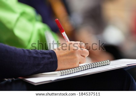 Close-up of Hands holding pens and making notes at the conference - stock photo