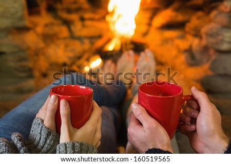 Close-up of hands holding red coffee cups in front of lit fireplace - stock photo
