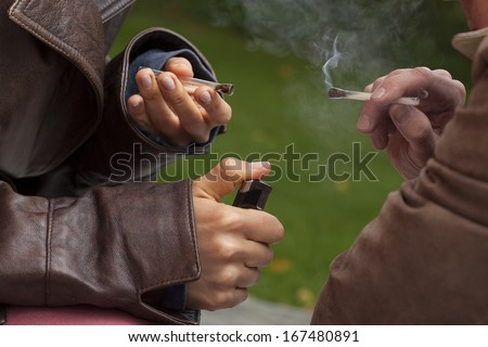 Close up of hands holding two burninig joints and thick smoke - stock photo