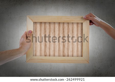 Close up of hands holding wooden blank frame. Place for text - stock photo