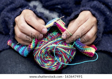 Close-up of hands knitting colorful wool - stock photo