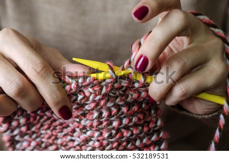 Close-up of hands knitting. Handmade scarf