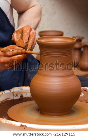 Close-up of hands making pottery on a wheel - stock photo