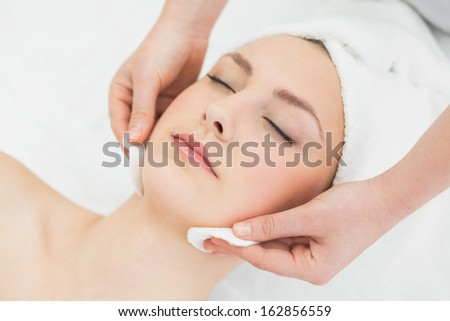 Close up of hands massaging a beautiful woman's face at beauty spa - stock photo