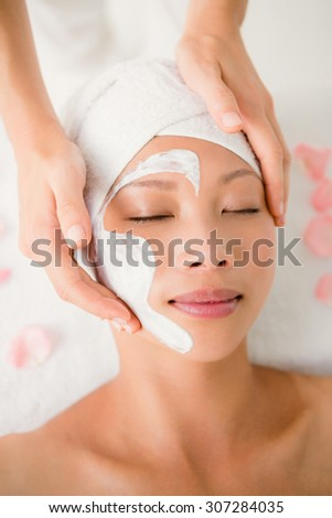 Close up of hands massaging a beautiful womans face at beauty spa - stock photo