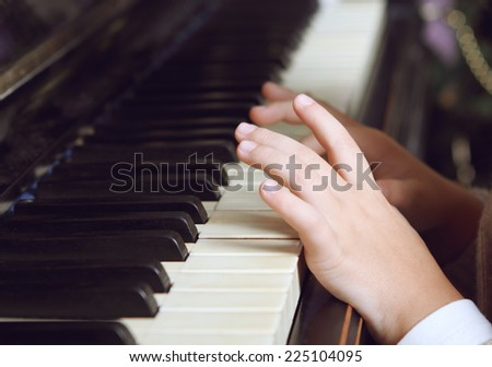 Close up of hands of a child playing the piano - stock photo
