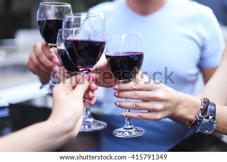 Close up of hands of a friends toasting in restaurant