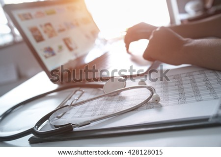 Close-up of hands of a nurse typing on laptop - stock photo