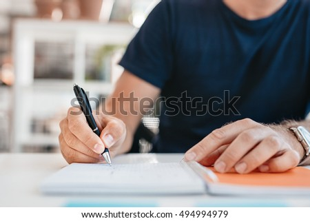 Close up of hands of a young man writing in a office diary. Focus on pen in hand of businessman.