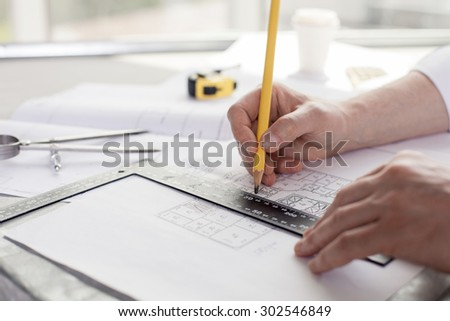 Close up of hands of architect drawing sketches of construction. He is holding a pencil and a ruler - stock photo
