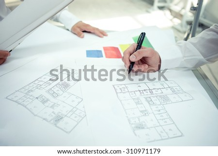 Close up of hands of architects drawing sketches of construction. There are blueprints on the table - stock photo