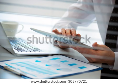 Close-up of hands of business man working on a tablet computer. - stock photo