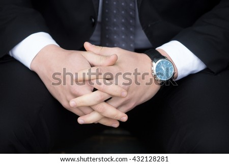 Close-up of hands of confident young business man wearing formal black suit and watch. Successful attractive caucasian businessman - stock photo