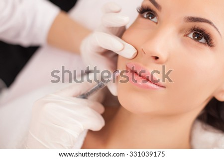 Close up of hands of cosmetologist making botox injection in female lips. She is holding syringe. The young beautiful woman is receiving procedure with enjoyment - stock photo