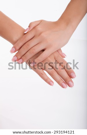 Close up of hands of elegant woman crossing her palms gently. Beautyful nails. Isolated on white - stock photo