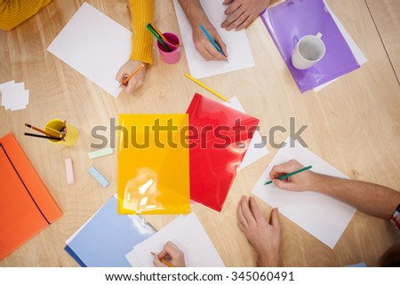 Close up of hands of four designers sitting at the desk. The men are women are drawing sketches with inspiration - stock photo