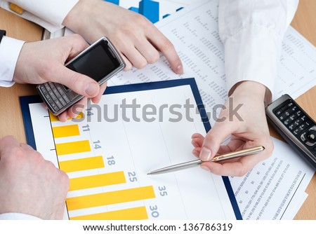 Close up of hands of managers discussing diagram and sitting at the office table with heap of documents - stock photo