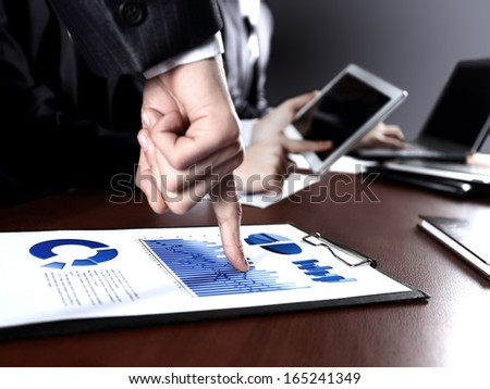 Close up of hands of managers discussing diagram and sitting at the table - stock photo