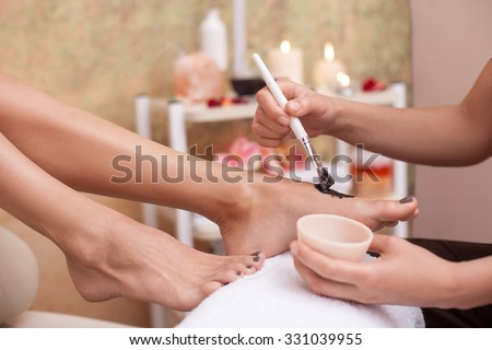 Close up of hands of masseuse applying chocolate substance on female legs during massage. The woman is sitting and holding the bowl with brush - stock photo