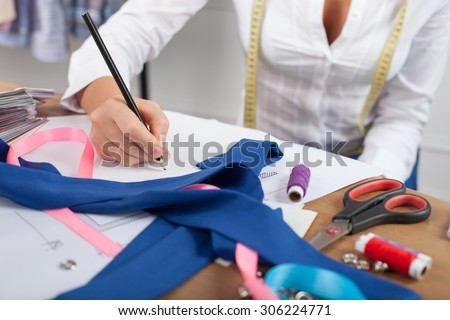 Close up of hands of skilled fashion designer. The woman is sitting at the table. She is drawing sketches of clothes on a blueprint. There are many design things on the desk - stock photo