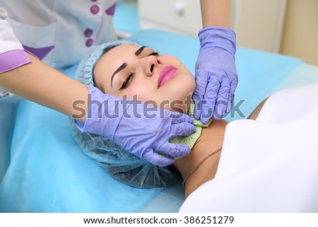 Close up of hands of skillful beautician cleaning and touching female face with sponge. The woman is lying and relaxing. Her eyes are closed with pleasure.