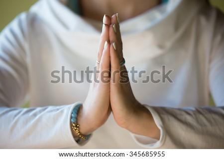 Close-up of hands of sporty young beautiful woman in white clothes meditating indoors, focus on arms in Namaste gesture - stock photo