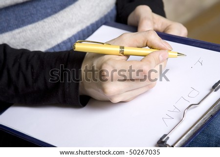 Close-up of hands of the girl who wrote on a white sheet of paper the text of the Plan