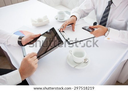 Close up of hands of two businessmen sitting at the table in restaurant. They are doing their work. One man is holding a laptop. Another businessman is writing down main ideas and holding phone - stock photo