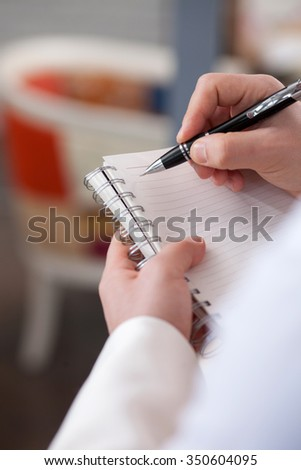Close up of hands of waiter receiving an order of customer. He is standing and writing. The man is holding a notebook and pen - stock photo